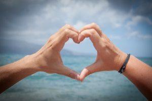 Aus Händen geformtes Herz als Erklärumg für Wie verlieben sich Männer